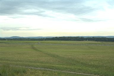 A view from the Union position looking across towards Seminary Ridge. The monument just visible in front of the screen of trees is the Virginia State Monument. If one drew a line from this viewpoint, back toward the State Monument it would follow the route taken by Pickett's division. (Copyright Allen Goodall 2003)